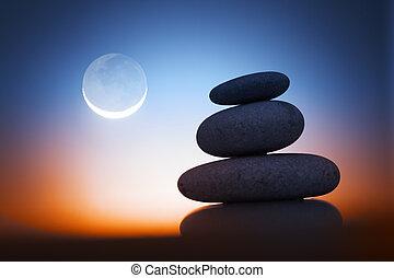 Zen stones at night - Stack of zen stones over sunrise sky...