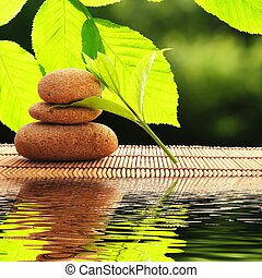 zen stones and water reflection showing spa concept