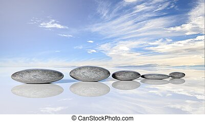 Zen stones row from large to small  in water reflecting peaceful sky with clouds.
