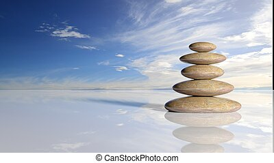 Zen stones stack from large to small in water reflecting peaceful sky with clouds.