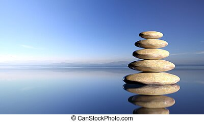 Zen stones stack from large to small in water with blue sky...