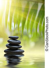 Zen stones - Green bamboo leaves over zen stones pyramid...