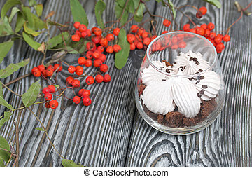 Zephyr in a glass. With biscuit and chocolate. Nearby are several branches of mountain ash with red berries. On pine boards painted black and white.
