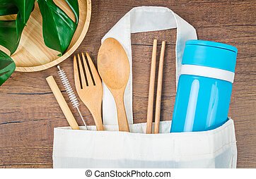 Zero waste concept. Textile eco bags, wooden glass and bamboo utensil on wooden background.