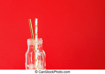 Zero waste. Paper recycable drinking cocktail party straws in glass vintage bottle on red background.