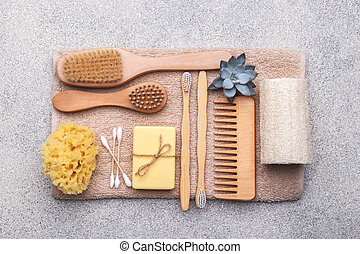 Zero waste reusable bathroom items on natural stone background, wooden comb, tooth brush, sea sponge, ear sticks, solid soap, shea or coconut butter