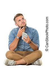 zich het denken, smartphone, zittende , vloer, jonge, terwijl, vasthouden, man