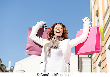 zij, liefdes, shopping., laag hoek overzicht, van, vrolijke , jonge vrouwen, staand, met, haar, hands verheven, en, vasthouden, de, het winkelen zakken