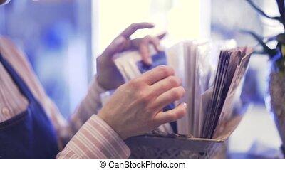 zijaanzicht, van, een, verkoopster, kies, wikkelend papier,...