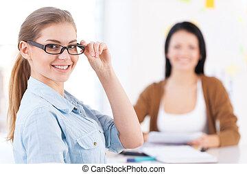 zijn, collega's, vrouw, haar, werkende , jonge, terwijl, vrolijk, team., fototoestel, achtergrond, deel, het glimlachen, bril, vrolijke