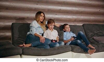 zijn, mensen, woning, zittende , house., twee, spelend, draadloos, joystick., zonen, video, sofa, spelen, moeder, vrolijke