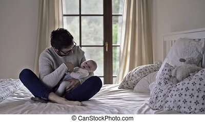 zijn, zittende , vader, bed, jongen, vasthoudende baby