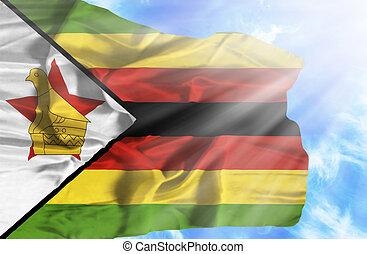 Zimbabwe waving flag against blue sky with sunrays
