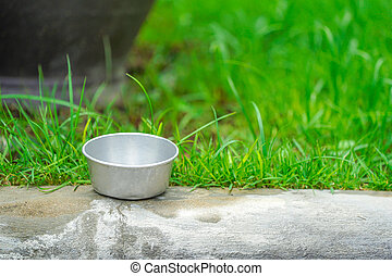 zinc cup on the foot-part with green garden background.