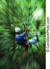 Man speeding on zip-line in forest canopy