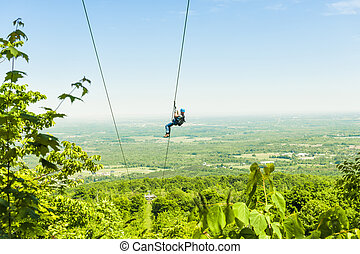 Zip-lining - Young woman zip-lining with aerial countryside...