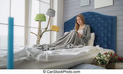 zittende , bed., terwijl, boek, blonde, lezende