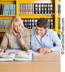 zittende , bibliotheek, het kijken, terwijl, boek, student, leraar
