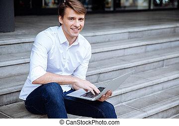 zittende , draagbare computer, buitenshuis, gebruik, man, vrolijke