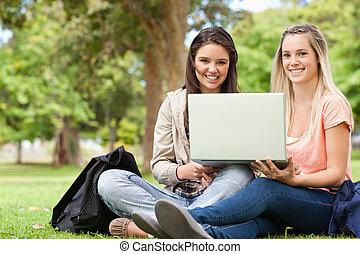 zittende , draagbare computer, tieners, terwijl, gebruik, het glimlachen