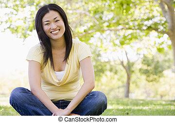 zittende , glimlachende vrouw, buitenshuis