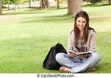zittende , schoolboek, terwijl, tiener, vasthouden, het glimlachen
