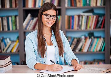 zo, vrolijke , om te, zijn, een, student!, mooi, jonge vrouw , schrijvende , iets, in, haar, opmerking blok, en, kijken naar van fototoestel, terwijl, zittende , op, de, bureau, in, de, bibliotheek