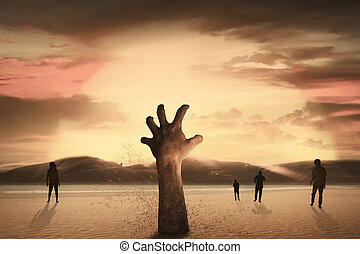 Zombie hand rising out from the ground