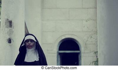 zombie nun. devilish woman in nun costume walking around the...