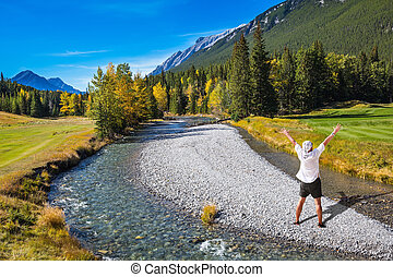 Zonked tourist in white shirt and bandana stands on a rocky shoal creek. Autumn day in the Canadian Rockies, Banff Park
