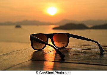 zonnebrillen, op, ondergaande zon