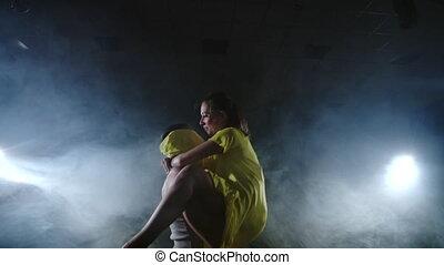Zoom camera, a female dancer jumps onto her partner...