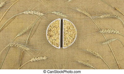 Zoom dish with oat grains and spikelets of wheat lying on sackcloth.