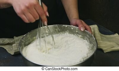 zoom in female hands slowly mixing by whisk white flour with...