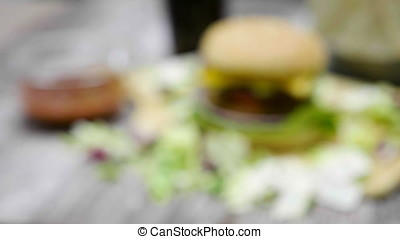 Zoom in from out of focus on home made hamburger with fries on wooden table