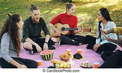 Zoom-in of attractive girl playing the guitar on picnic while her friends are listening to music and singing then clapping hands. Outdoor activities and friendship concept.