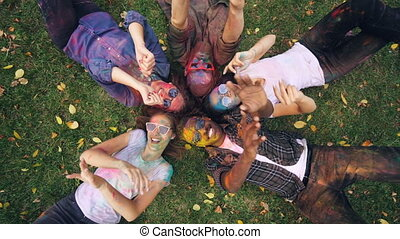 Zoom-in of relaxed people multi-ethnic group lying on grass...