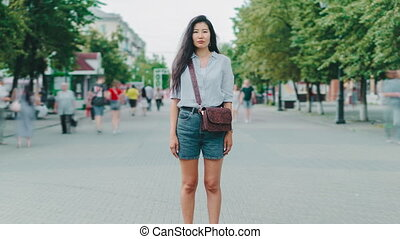 Zoom-in of serious Asian girl in casual clothes standing outdoors in city street
