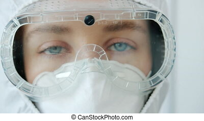 Zoom-in portrait of serious woman doctor wearing safety uniform mask, suit and respirator during covid-19 quarantine. Infection outbreak and medicine concept.