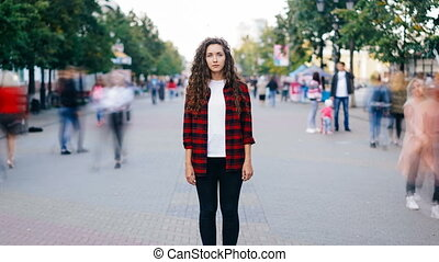 Zoom in time-lapse of beautiful girl with long curly hair standing in street looking at camera when many men and women are walking around in hurry on summer day.