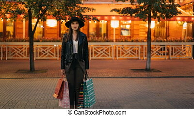 Zoom in time-lapse of pretty girl in trendy clothing standing with shopping bags in busy street and looking at camera when crowds of people are passing by.