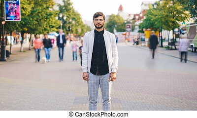 Zoom in time-lapse of young businessman in trendy garments...