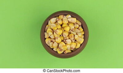 Zoom of a clay pot filled with corn grain. Isolated green screen.