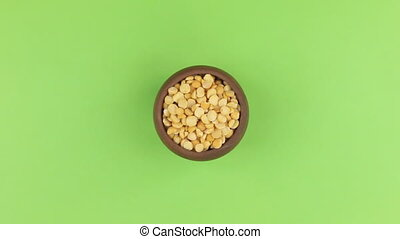 Zoom of a clay pot filled with peas grain. Isolated green screen.