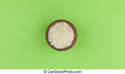 Zoom of a clay pot filled with rice grain. Isolated green screen.