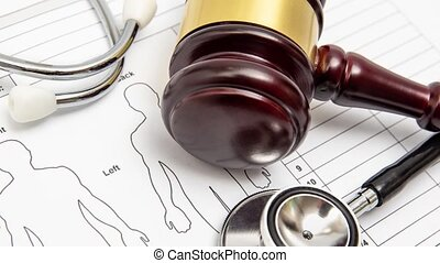 Zoom out. A wooden judge gavel and stethoscope on a medical chart. Medical dispute concept.