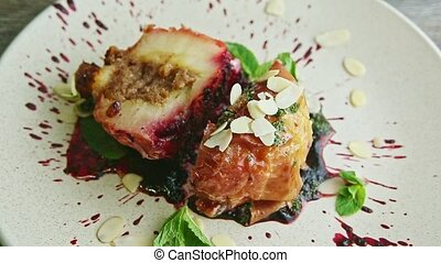zoom out from exquisite decorated sliced stuffed with raisins baked apple served with fruit syrup, nuts, and fresh mint on modern restaurant plate