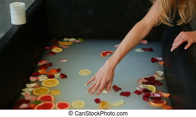 zoom out from woman mix citrus slices and rose petals in...