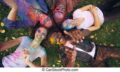 Zoom-out of cheerful friends multiracial group resting on...
