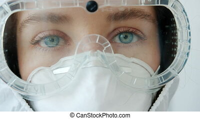 Zoom-out close-up portrait of female medic in quarantine suit,respirator and goggles standing indoors on white background and looking at camera.